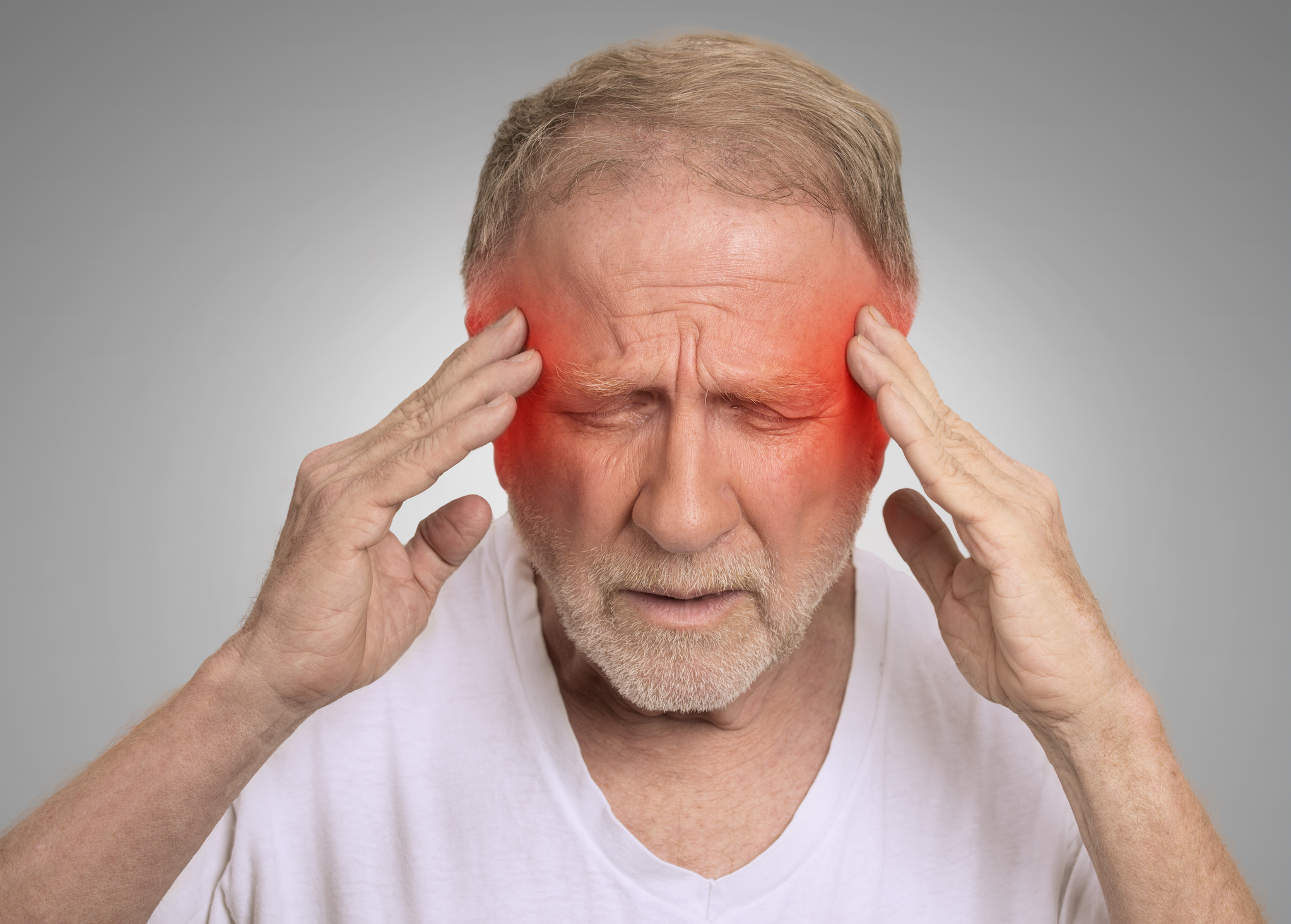 man with migraine rubbing his head with red inflamed areas on temples